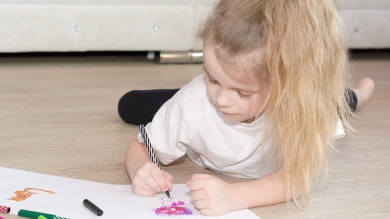 Child colouring-in whilst lying on the floor